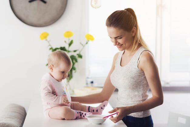 La mujer va a alimentar al bebé con alimentos para bebés.