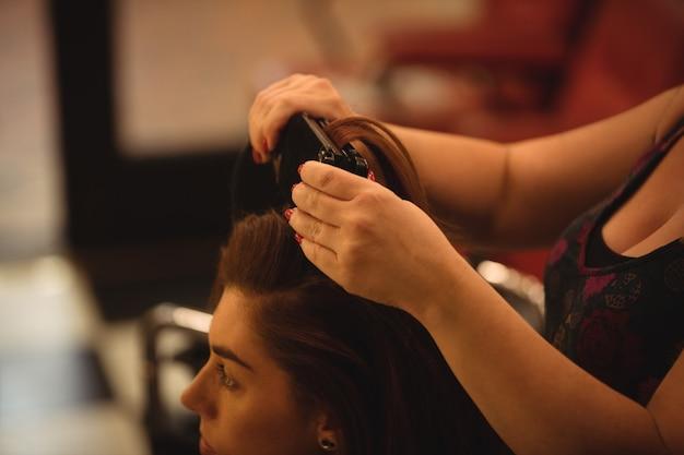 La mujer se está alisando el cabello