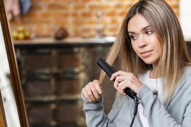 Mujer alisándose el cabello en casa