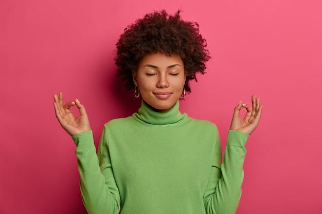 Mujer aliviada alcanza el nirvana, se para en posición de loto, medita después del trabajo, cierra los ojos y respira profundamente, intenta aliviar el estrés, practica yoga en interiores