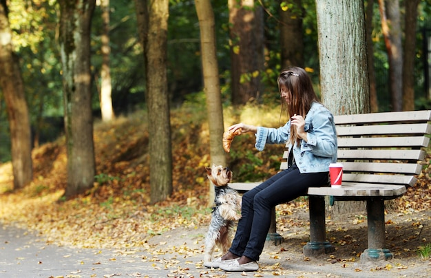 Mujer almorzar paseando con su perro