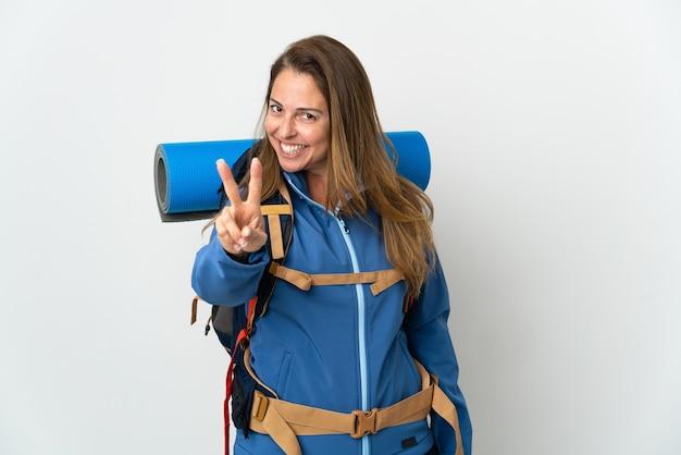 Mujer alpinista de mediana edad con una gran mochila aislada
