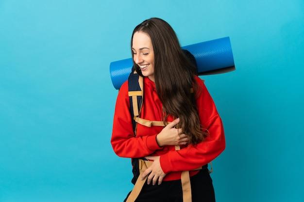 Mujer alpinista con una mochila grande sobre fondo aislado sonriendo mucho