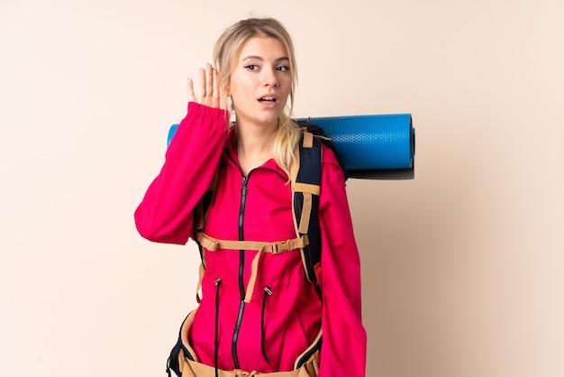 Mujer alpinista con una mochila grande sobre pared aislada escuchando algo