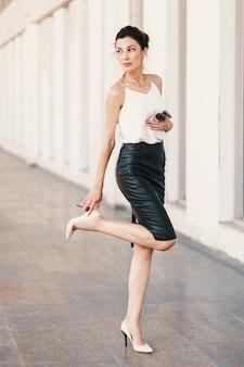 Mujer alta tocando el talón negro en su zapato desnudo mientras mira por encima del hombro al aire libre.