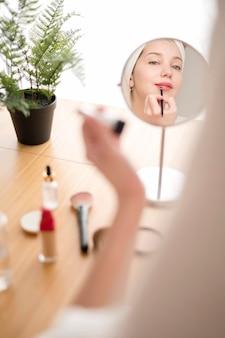 Mujer de alto ángulo aplicando lápiz labial