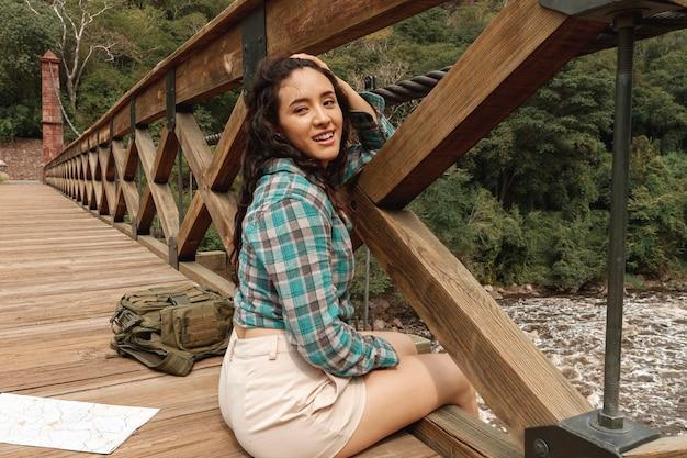 Mujer de alto ángulo descansando sobre el puente
