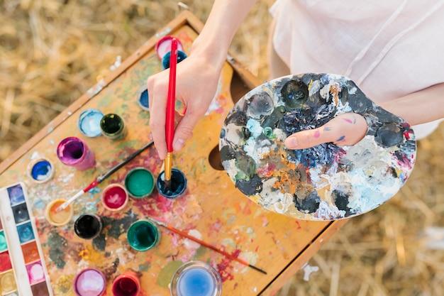 Mujer de alto ángulo con elementos de pintura