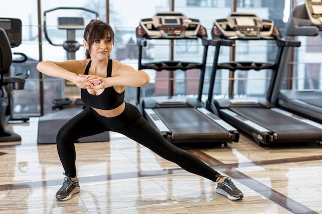Mujer de alto ángulo en estiramientos de gimnasio