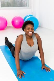 Mujer de alto ángulo haciendo ejercicio en mat