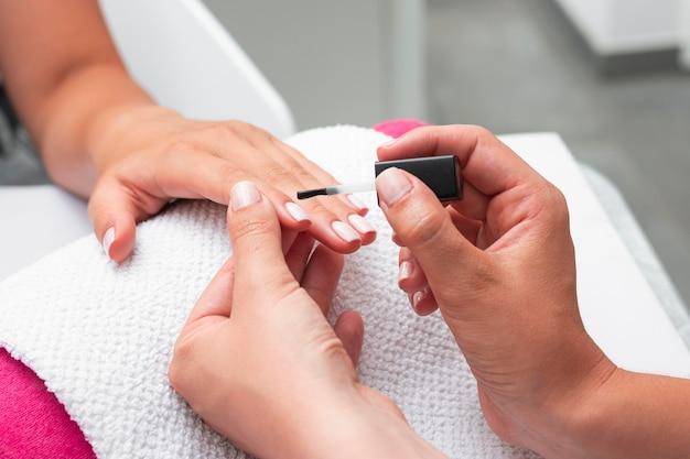 Mujer de alto ángulo haciendo la manicura de un cliente