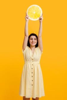 Mujer de alto ángulo con limón gigante