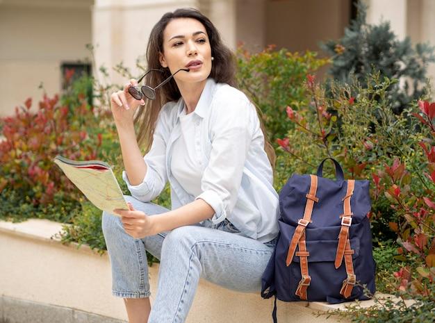 Mujer de alto ángulo con mochila y mapa