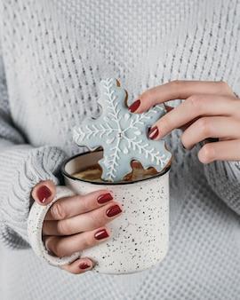 Mujer de alto ángulo mojar galletas de copo de nieve en chocolate caliente