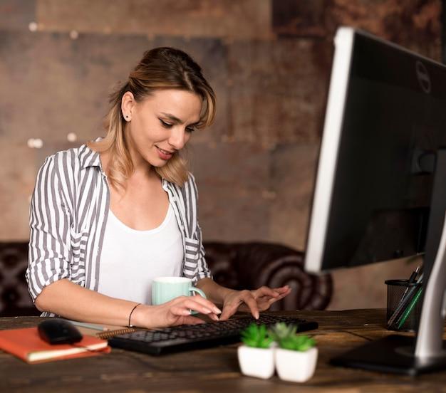 Mujer de alto ángulo que trabaja en la computadora
