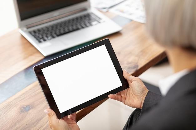 Mujer de alto ángulo que trabaja en la oficina en tableta