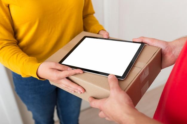 Mujer de alto ángulo y repartidor sosteniendo una caja y una tableta de pantalla vacía
