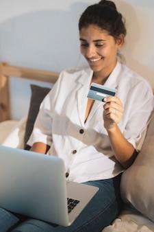 Mujer de alto ángulo sosteniendo una tarjeta y trabajando en la computadora portátil