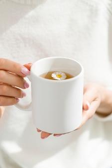 Mujer de alto ángulo con taza blanca con té