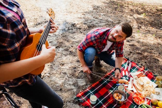 Mujer de alto ángulo tocando instrumento y hombre cocinando