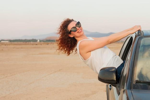 Mujer de alto ángulo en la ventanilla del coche
