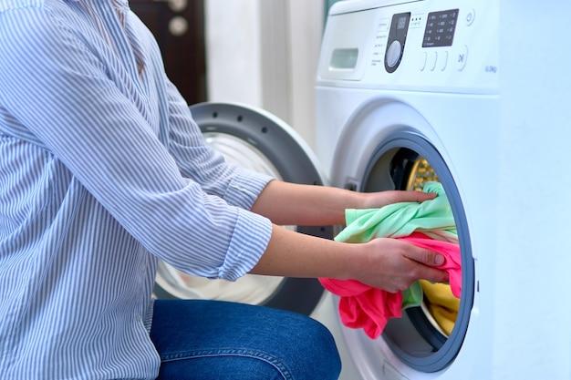 Mujer ama de casa carga lavadora con ropa de colores sucios en el día de lavandería