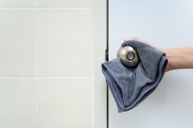 Mujer ama de casa limpiando una perilla de puerta de acero inoxidable sucio en el inodoro. sirvienta rociando solución de limpieza líquida en la manija de la perilla de la puerta sucia en el inodoro y usando un paño de microfibra en la superficie de la perilla de la puerta.
