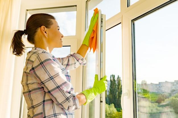 Mujer ama de llaves limpiando ventanas