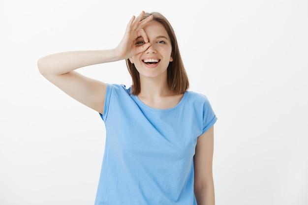 Mujer amable despreocupada riendo feliz y mostrando bien firmar sobre los ojos, todo bien, todo perfecto