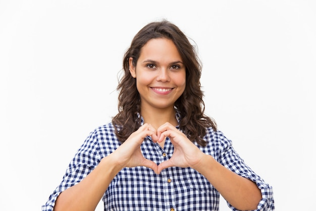 Mujer amable feliz haciendo forma de corazón con manos