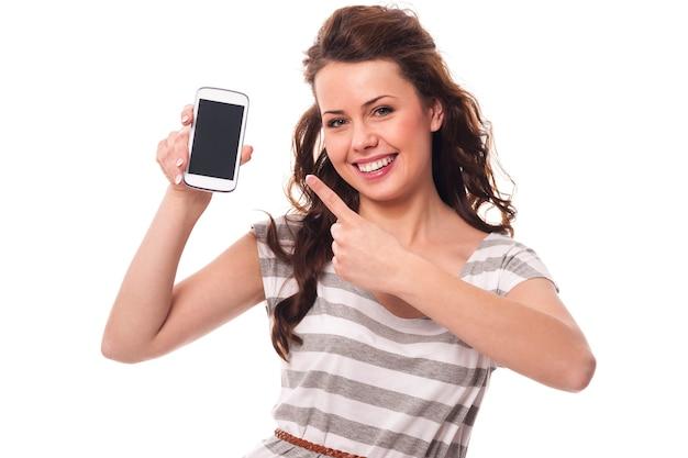 Mujer amable mostrando en la pantalla del teléfono móvil blanco