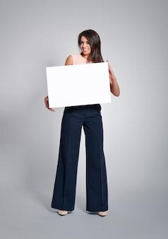 Mujer amable sosteniendo tablero vacío