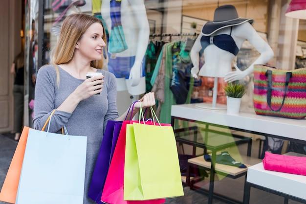 Mujer amante de las compras con la bebida que mira la exhibición de la ventana de t de una tienda