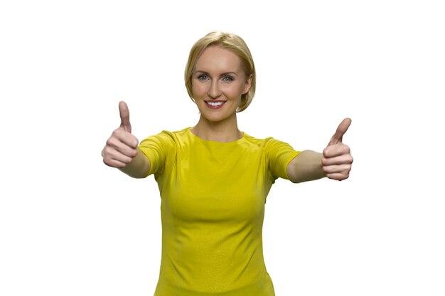 Mujer en amarillo mostrando bien con ambas manos en la pared blanca