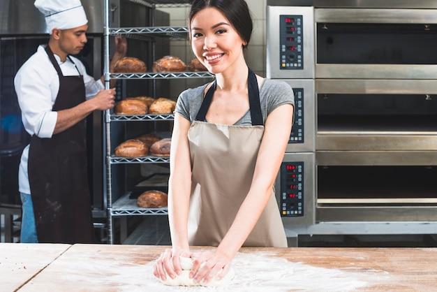 Mujer amasando la masa en la mesa de madera y panadero de sexo masculino con estantes de pan horneado