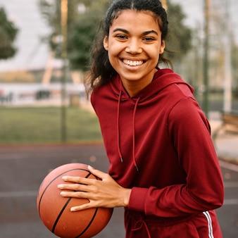 Mujer americana negra sonriente sosteniendo una pelota de baloncesto