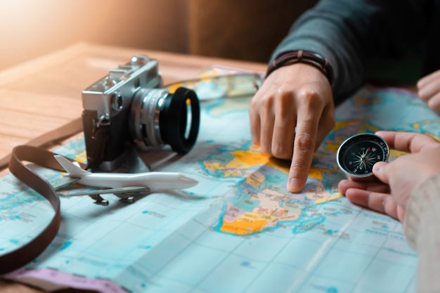 Mujer con amiga planeando viaje de vacaciones con accesorios de viajero
