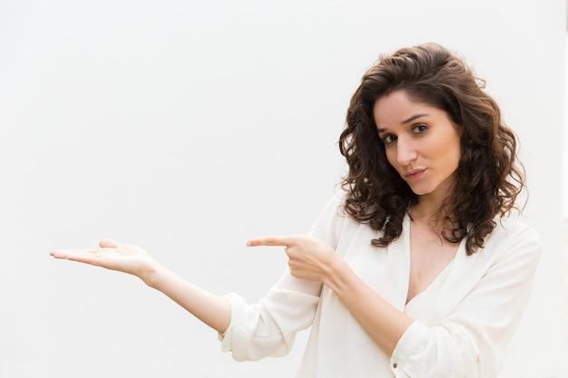 Mujer amigable positiva que señala el dedo y que sostiene el espacio de la copia