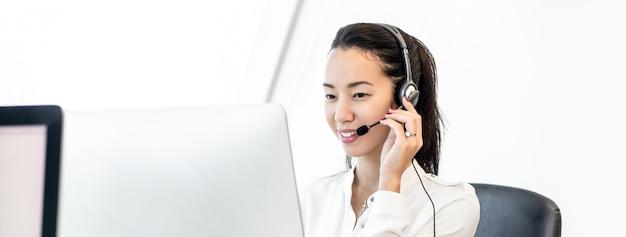 Mujer amistosa hermosa asiática sonriente en fondo de la bandera del centro de atención telefónica