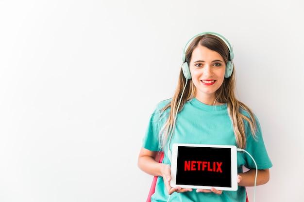 Mujer amistosa que muestra el logotipo de netflix