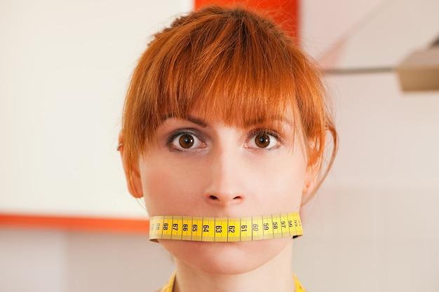 Mujer amordazada por una cinta métrica - símbolo para el trastorno alimentario