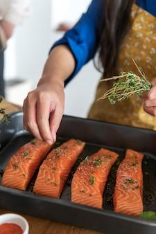 Mujer añadiendo especias y hierbas al salmón crudo