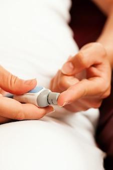 Mujer analizando glucosa para diabetes