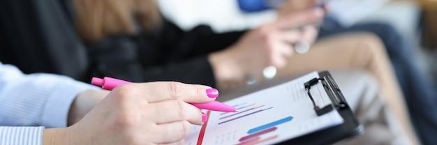 Mujer analizando gráfico sobre documentos en primer plano de la conferencia de negocios