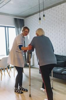 Mujer andando con enfermera en asilo de ancianos