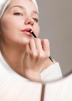 Mujer de ángulo bajo aplicar lápiz labial