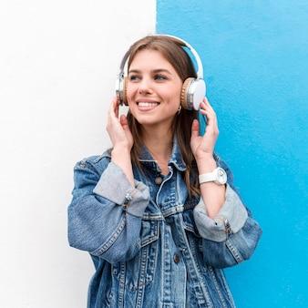 Mujer de ángulo bajo con auriculares
