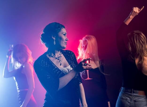 Mujer de ángulo bajo con bebida bailando