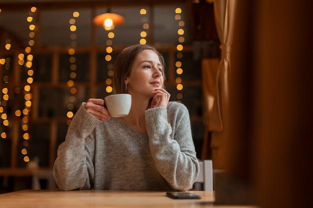 Mujer de ángulo bajo con café