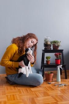 Mujer de ángulo bajo en casa abrazando gato